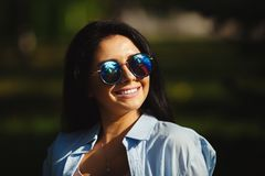Brunette with dazzling smile in sunglasses looking at the sun. Summer portrait of cute girl wearing circular glasses Stock Image