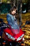 Brunette de fille avec une moto rouge Images libres de droits