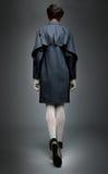 Brunette de modèle de mode dans la couche grise marchant loin Images libres de droits