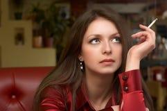 Brunette de ojos verdes con el cigarro Fotografía de archivo libre de regalías