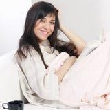 Brunette de sorriso com leitura da manta Imagens de Stock