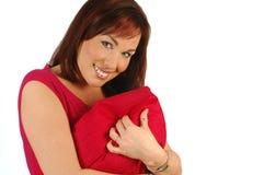 Brunette de sorriso em uma parte superior vermelha que prende um coxim Fotos de Stock Royalty Free