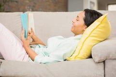 Brunette de sourire affichant un livre images stock