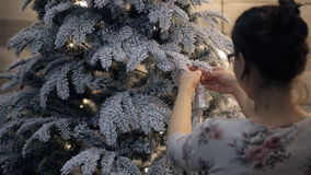 Brunette decorate Christmas tree with toy. View from back. stock video footage