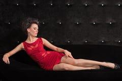 Brunette della giovane donna in vestito rosso che pone sul nero Fotografia Stock Libera da Diritti