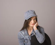 Brunette in Denim Hat with Elbow on Chair Royalty Free Stock Images