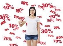 Brunette in denimborrels en wit mouwloos onderhemd die aan de borst op het concept de kortingen en de verkoop wijzen Royalty-vrije Stock Fotografie