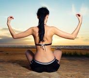 Brunette, der auf dem Strand nahe dem Meer sitzt Lizenzfreies Stockfoto