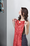 Brunette, der auf rotem Kleid versucht Lizenzfreie Stockbilder