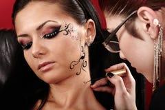 Brunette, der Gesichtstätowierung durch Maskenbildner angewendet wird Stockfotografie