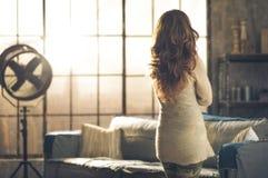 Brunette, der heraus industrielles schickes Dachbodenfenster schaut Stockbilder