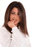 Brunette, der ihren Finger beißt Lizenzfreie Stockfotografie