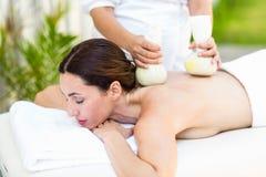 Brunette, der Massage mit Kräuterkompressen hat Lizenzfreie Stockfotos