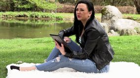 Brunette in der Natur mit einer Tablette stock video footage