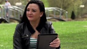 Brunette in der Natur mit einer Tablette stock footage