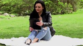 Brunette in der Natur mit einer Tablette stock video