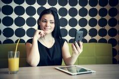 Brunette, der selfie Foto unter Verwendung eines Smartphone macht Lizenzfreie Stockfotos