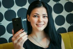 Brunette, der selfie Foto unter Verwendung eines Smartphone macht Lizenzfreies Stockbild