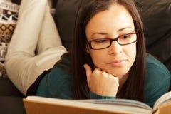 Brunette, der sich zu Hause mit Buch entspannt. Lizenzfreies Stockfoto