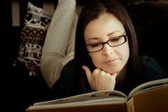 Brunette, der sich zu Hause mit Buch entspannt. Stockbild