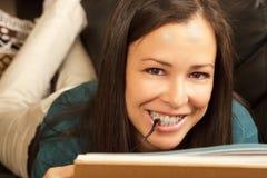 Brunette, der sich zu Hause mit Buch entspannt. Lizenzfreies Stockbild
