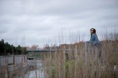 Brunette in der Sonnenbrille, die weg gegen Fluss schaut Lizenzfreies Stockbild
