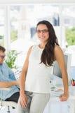 Brunette designer smiling at camera leaning on desk Stock Photography