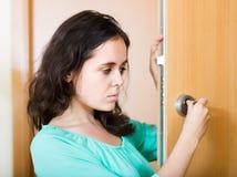 Brunette die gebroken slot van deur bekijken stock fotografie