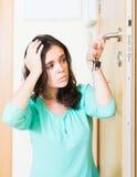 Brunette die gebroken slot van deur bekijken stock foto