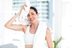 Brunette die haar voorhoofd met handdoek afvegen stock foto's