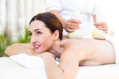 Brunette die massage met kruidenkompressen hebben Royalty-vrije Stock Foto's