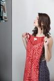 Brunette die op rode kleding probeert Royalty-vrije Stock Afbeeldingen