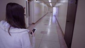 Brunette die op smartphone spreken die onderaan de gang met deuren lopen stock footage
