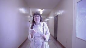 Brunette die op smartphone spreken die onderaan de gang met deuren lopen stock videobeelden