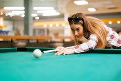Brunette die terwijl het spelen van snooker streven stock foto's