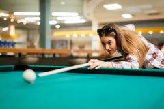 Brunette die terwijl het spelen van snooker streven stock afbeeldingen