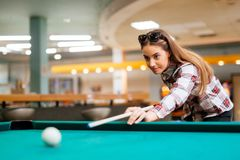 Brunette die terwijl het spelen van snooker streven stock foto