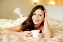 Brunette die van koffie in bed genieten stock afbeeldingen
