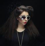Brunette die zonnebril dragen die in de studio stellen Stock Foto