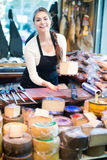 Brunette with different types of cheese in gastronomy. Happy spanish female brunette with different types of cheese in gastronomy Royalty Free Stock Image