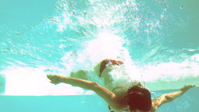 Brunette diving underwater in swimming pool Royalty Free Stock Photos