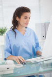 Brunette doctor using mouse of computer. In medical office stock photography