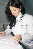 Brunette doctor writes anamnesis after consultation Stock Photo
