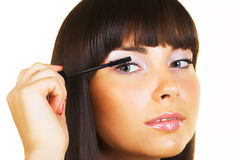 Brunette doing makeup Royalty Free Stock Photos