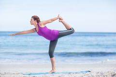 Brunette doing yoga on exercise mat Stock Photography