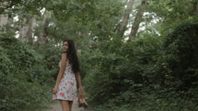 Brunette in a dress goes barefoot on the road in stock video