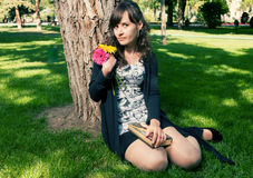 Brunette in dress sitting on grass near tree Stock Photography