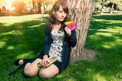 Brunette in dress sitting on grass near tree Royalty Free Stock Photography