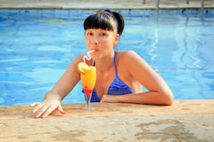 Brunette drinking cocktail in the pool Royalty Free Stock Image