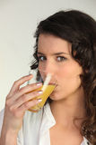 Brunette drinking glass of juice Royalty Free Stock Photography